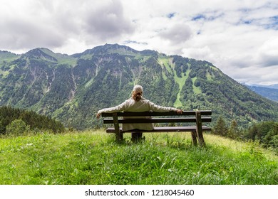 Women sitting on a bench looking at the alpine landscape in the Allgau. Bavaria. Germany.