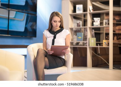 Women sitting on the couch with a folder in hand