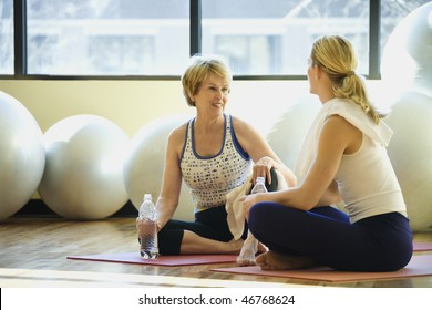 Women sitting on exercise mats and socializing while on break at the gym. Exercise balls are in the background. Horizontal shot.
