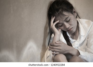 Women sitting on the floor crying with depression, Depressed woman sitting on ground, family problems, kitchen, abuse, Domestic violence, The concept of depression and suicide.