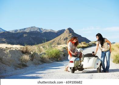 Women sitting on motorbike and sidecar