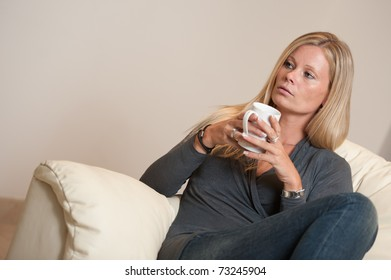 Women sitting on a sofa with a hot drink/coffee/tea mug.