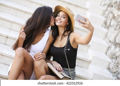 Women sitting on the stairs and taking selfie