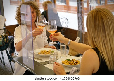 Women sitting in restaurant eating food with table shield to protect infection from coronavirus covid-19, restaurant and social distancing concept. Turin, Italy - May 2020