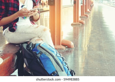 women sitting use a smart phone and travel bag