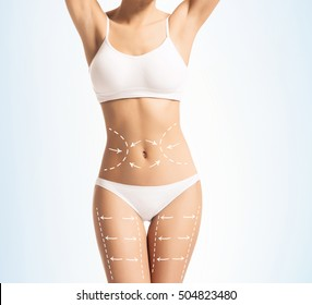 Women slim body in swimwear having arrows along her stomach and legs. Fat lose, liposuction and cellulite removal concept.