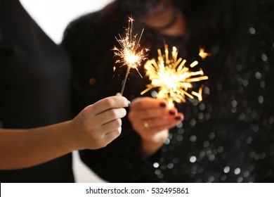 Women with sparklers, close up view