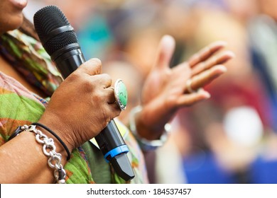 Women Speaking in to the microphone at the conference. Detail