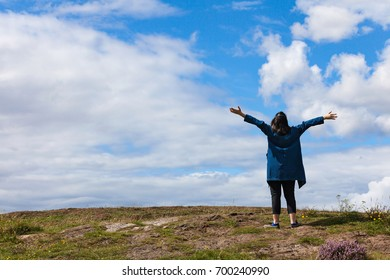 women stand on the hill and holds her arms, freedom and success