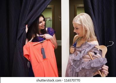 Women standing in a changing room of a boutique talking