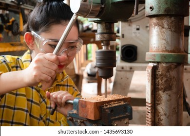 Women standing is craft working drill wood at a work bench with Drill Press power tools at carpenter machine in the workshop