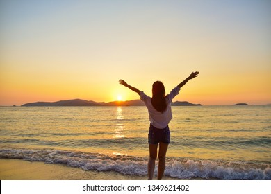Women standing on beach at sea sunset background on evening golden hour.Travel summer holiday sea beach in Thailand