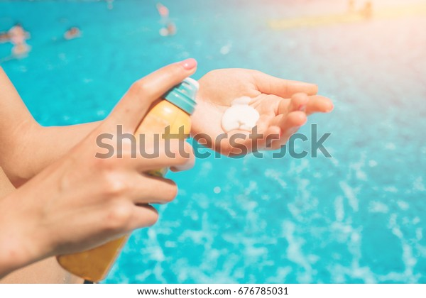 women standing on the beach and using suncream. close up of women hands receiving sunblock cream lotion .Female hands with sun protection cream on sky background. Skin care concept