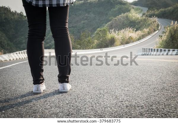 Women standing on long road