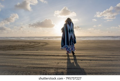 Women stands on Pacific Northwest beach at sunset, wrapped in blanket.