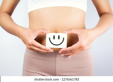 Women Stomach Health. Healthy Female With Beautiful Fit Slim Body  Holding White Card With Happy Smiley Face In Hands Good Digestion Concepts. High Resolution