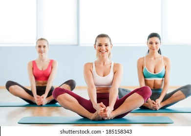 Women stretching. Three beautiful young women in sports clothing stretching and smiling