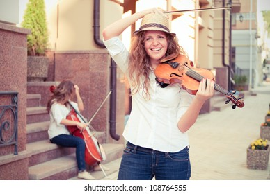 Women strings duet playing violin and cello on the street. Split toning