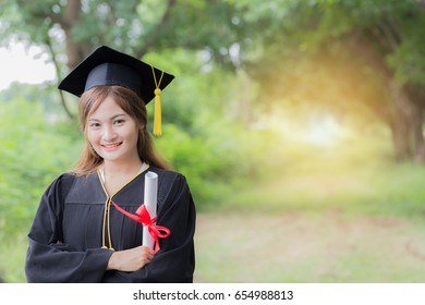 Women Student Graduate holding certificate in her hand and feeling so proud and happiness in Commencement day