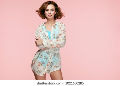 Women Style. Fashionable Young Model In Fashion Clothes. Portrait Of Sexy Smiling Girl Wearing Fashionable Clothes Touching Her Head And Curly Hair On Pink Background. High Resolution.