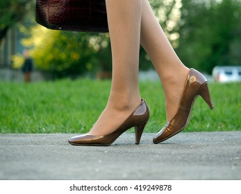 Women sumptuous legs in high heel shoes. Walk in the city, on the sidewalk. Summer, heat, green grass.