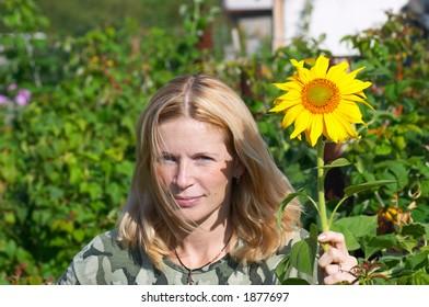 Women and sunflower. Sibir. Russia.