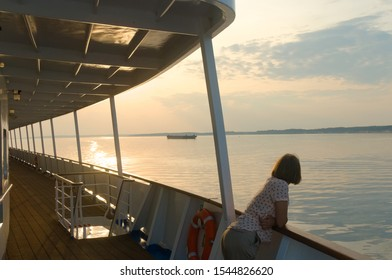 Women and the sunset on the river. Woman from the deck of a cruise boat watching at the sunset and a barge. The photo was taken on the Volga River near Kazan, Russia