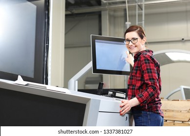 Women support a printing machine. Computer controlling the printing process.