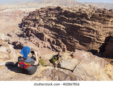 Women takes photo from the cliff edge of High Place of Sacrifice. Petra. Jordan.