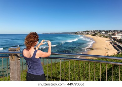 A women takes a photo with her smart phone of Bar Beach and Merewether - Newcastle Australia. The Newcastle region is home to some amazing coastline.