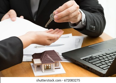 Women taking keys from real estate agent and discussing mortgage after signing rental lease contract, loan, purchase agreement for new home and calculate the amount to be paid to the bank