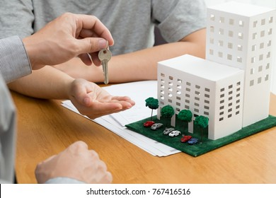 Women taking keys from real estate agent and discussing mortgage after signing rental lease contract, loan, purchase agreement for new condominium and calculate the amount to be paid to the bank
