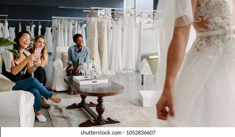 Women taking photographs of a female friend trying on wedding dress. Women in wedding dress fitting room.