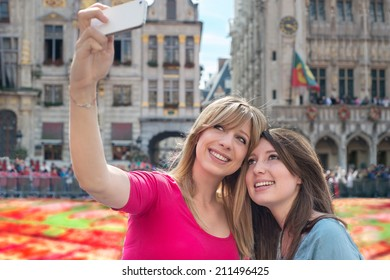 women taking a self portrait with smartphone against flower carpet in Grand Place, Brussels, Belgium
