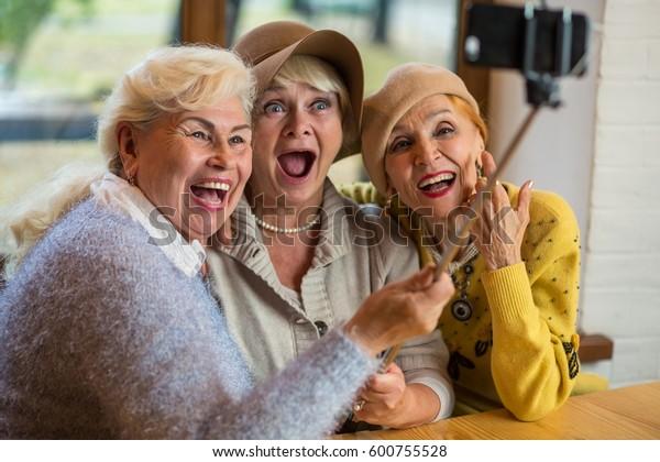 Frauen, die sich am Tisch selbst stellen. Drei hohe Damen lachen. Freundschaft ist unbezahlbar.
