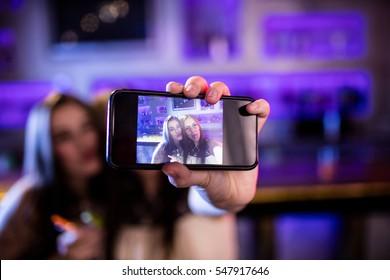 Women talking selfie from mobile phone in restaurant