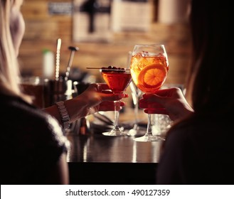 Women toasting with cocktails in bar