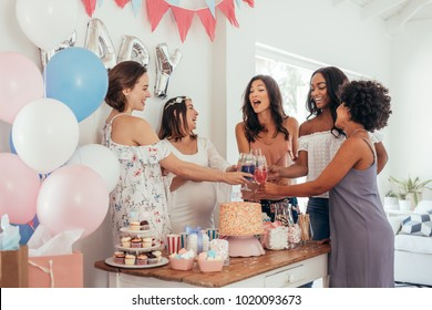 Women toasting with juices at baby shower party. Group of friends at baby shower party having juices.