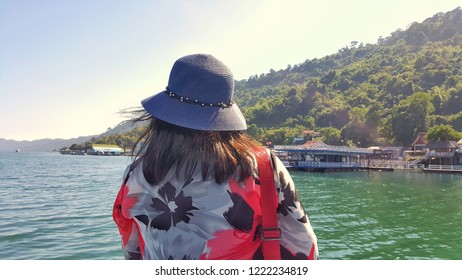 Women tourist looking at houseboat home stay in river with mountain view at thailand.