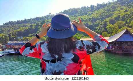 Women tourist looking at houseboat home stay in river with mountain view at lao.