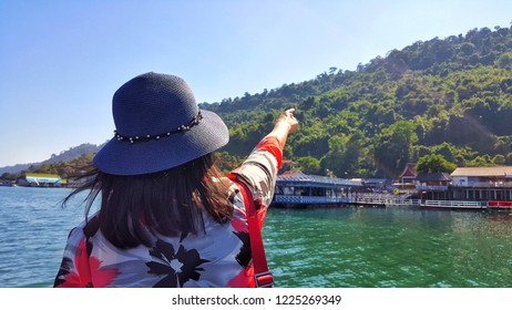Women tourist looking at houseboat village in river with mountain view at thailand.