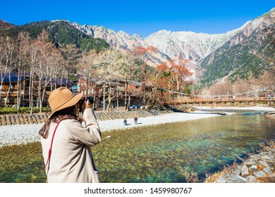 Women tourist take photo at the Kappa wodden bridge at Kamikochi, the northern part of the Japan Alps. Beautiful scenery .There are many natural and adventure hiking trails at Nagano Prefecture,Japan