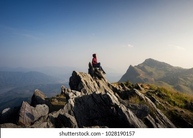 Women tourists sit at the top of the rock, Beautiful view point Sunset of travel place at Doi Pha Tang, Chiang Rai's Hidden Paradise,Thailand.