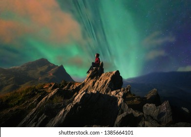 Women tourists sit at the top of the rock with Northern Lights or Aurora Borealis, Beautiful landscape.