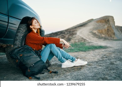 women tourists sitting near the car in nature