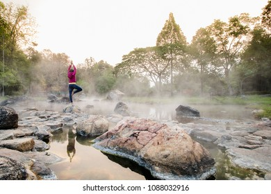 Women tourists stand above the natural hot springs with steam and green trees. She exercises in the morning by pretending to be a yoga practitioner.