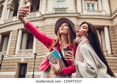 Women tourists taking selfie going sightseeing in Odessa. Happy friends travelers having fun