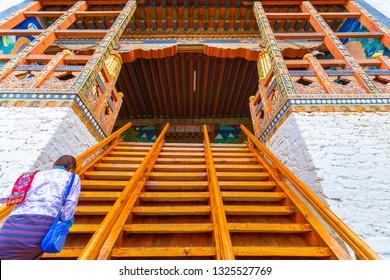 a women in traditional bhutanese cloth walk up to the Punakha Dzong Monastery, Punakha, Bhutan
