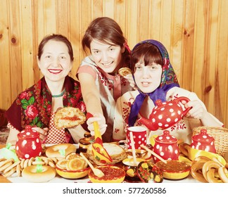 Women in traditional  clothes eating pancake with caviare during  Shrovetide