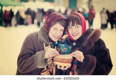 Women  in traditional  clothes eating pancake during  Pancake Week